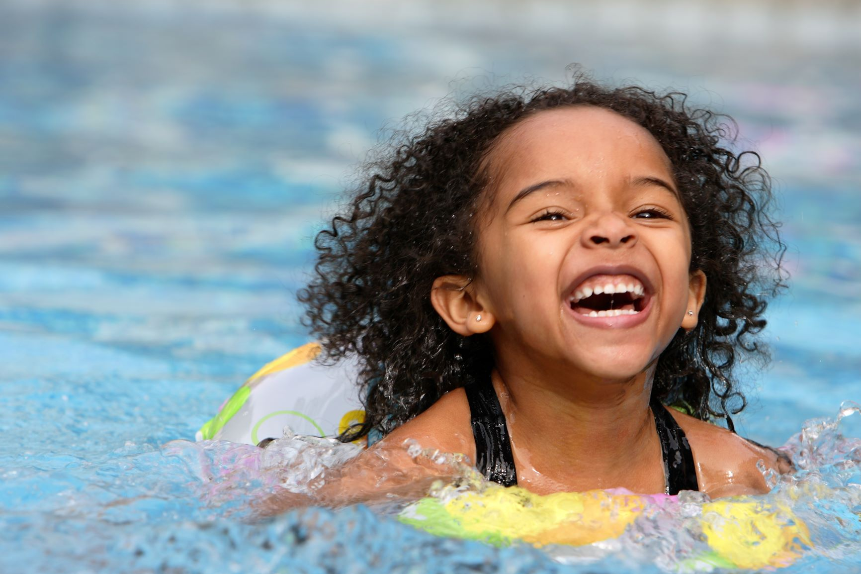 Young girl laughing while swimming.