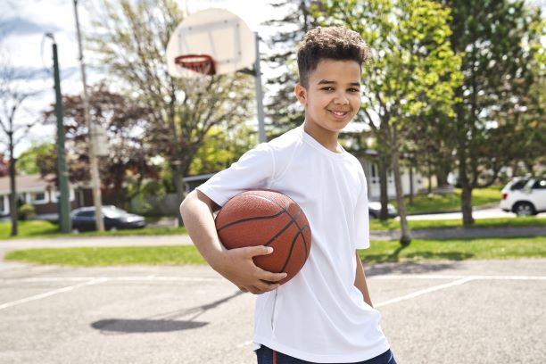 Adolescent boy holding a basketball on the court with net in background.