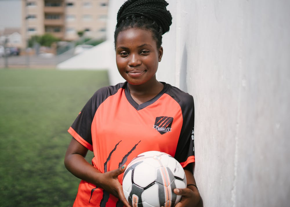 Youth female holding soccer ball in her uniform.