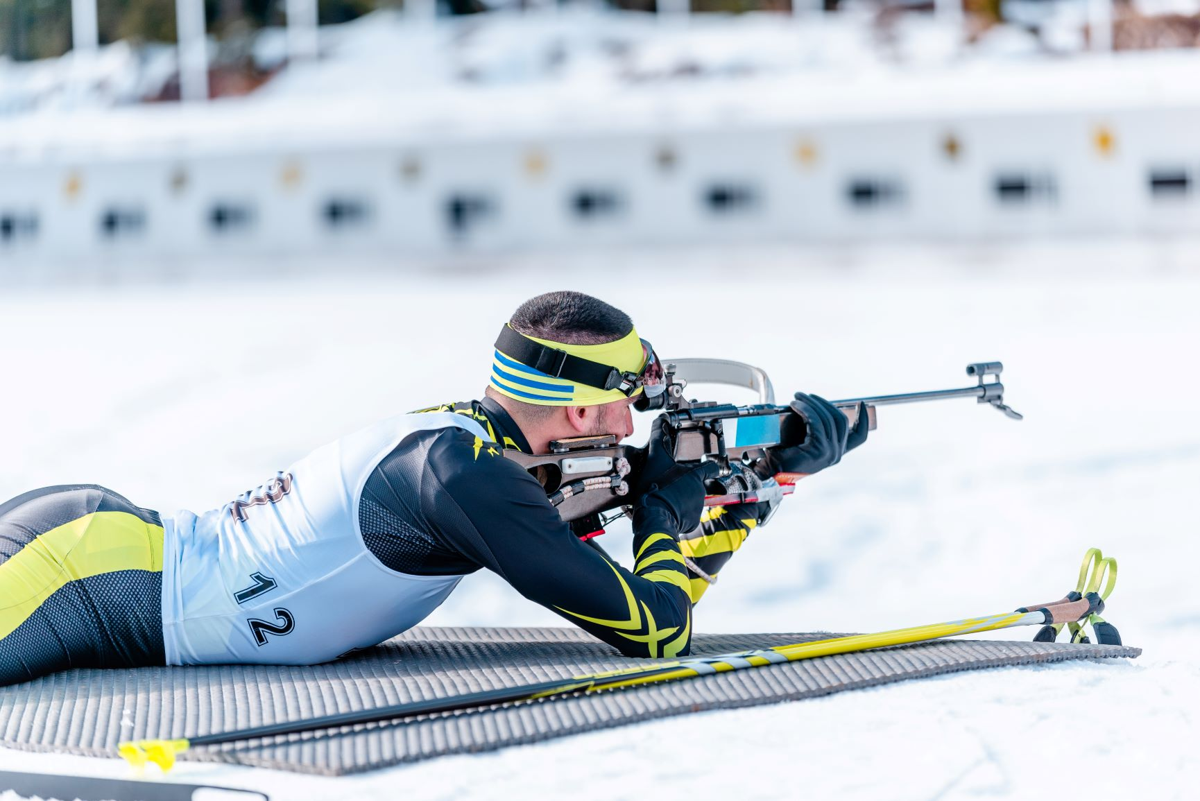 Biathlete rifle shooting lying position. Shooting range in the background. Race concept