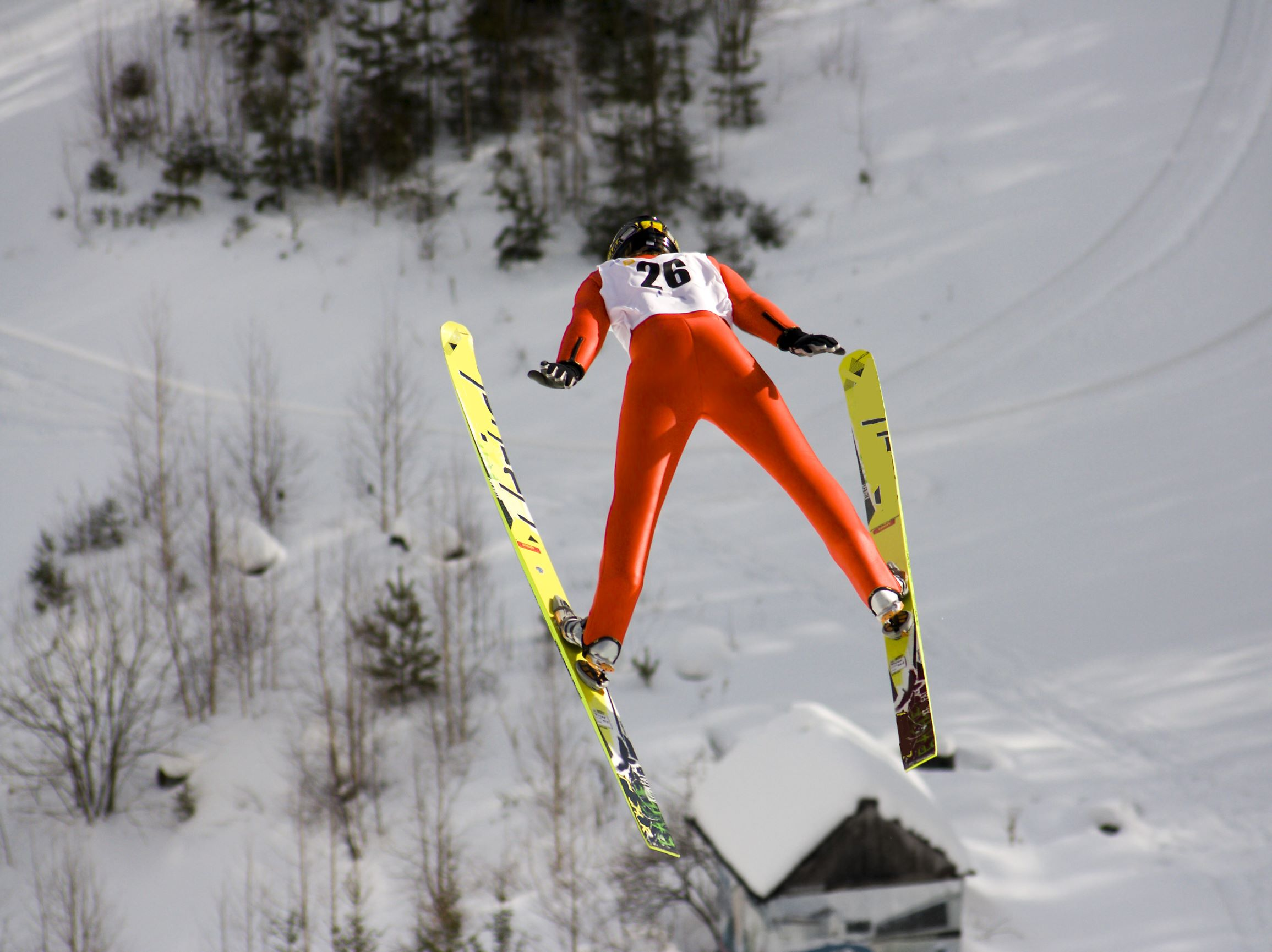 Competitive ski jumper flying through the air after leaving the ramp