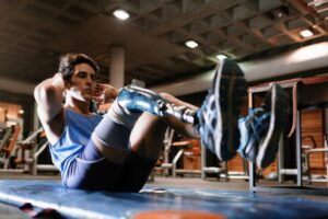 Young male athlete with a disability training in a gym, unhappy