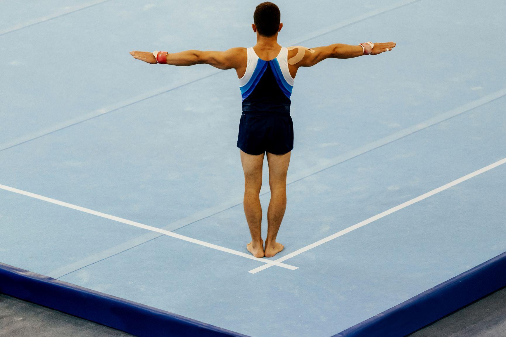 Male gymnast beginning floor routine.
