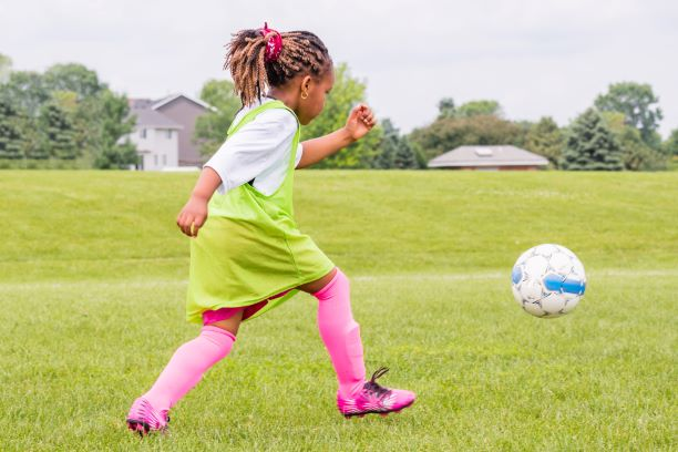 young girl learning to play soccer