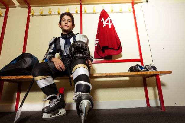 young male hockey player in dressing room