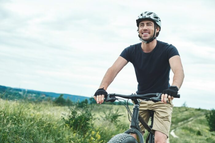 Man recreationally cycling through some fields