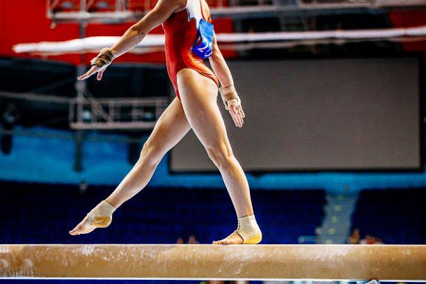 Female gymnast walks on balance beam