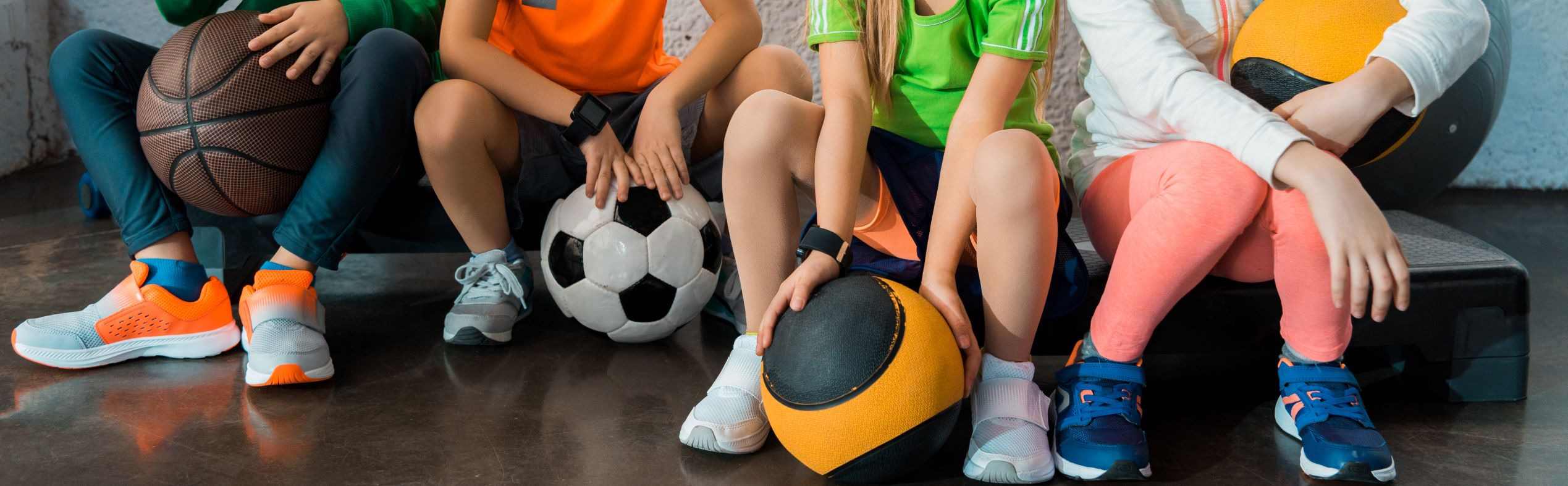 Cropped view of children sitting on step platforms with balls in gym, panoramic shot