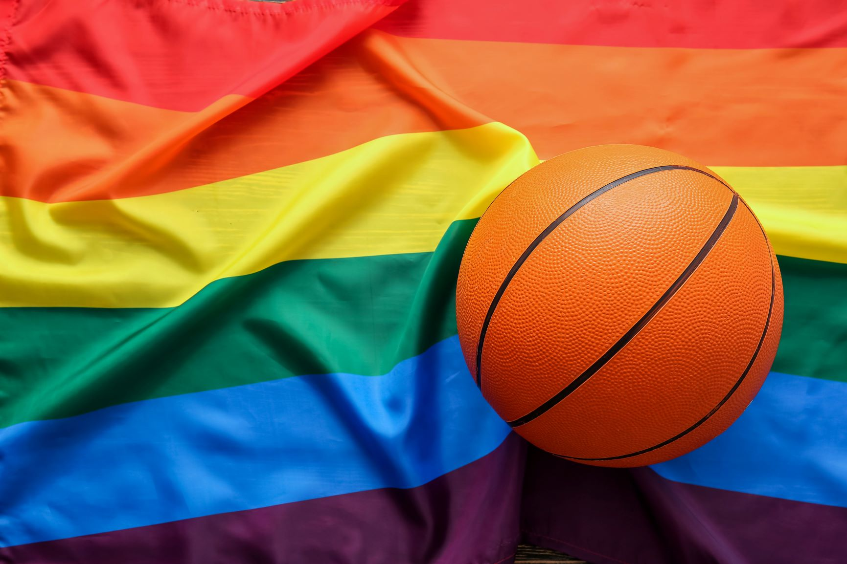 Basketball ball against lgbt rainbow flag