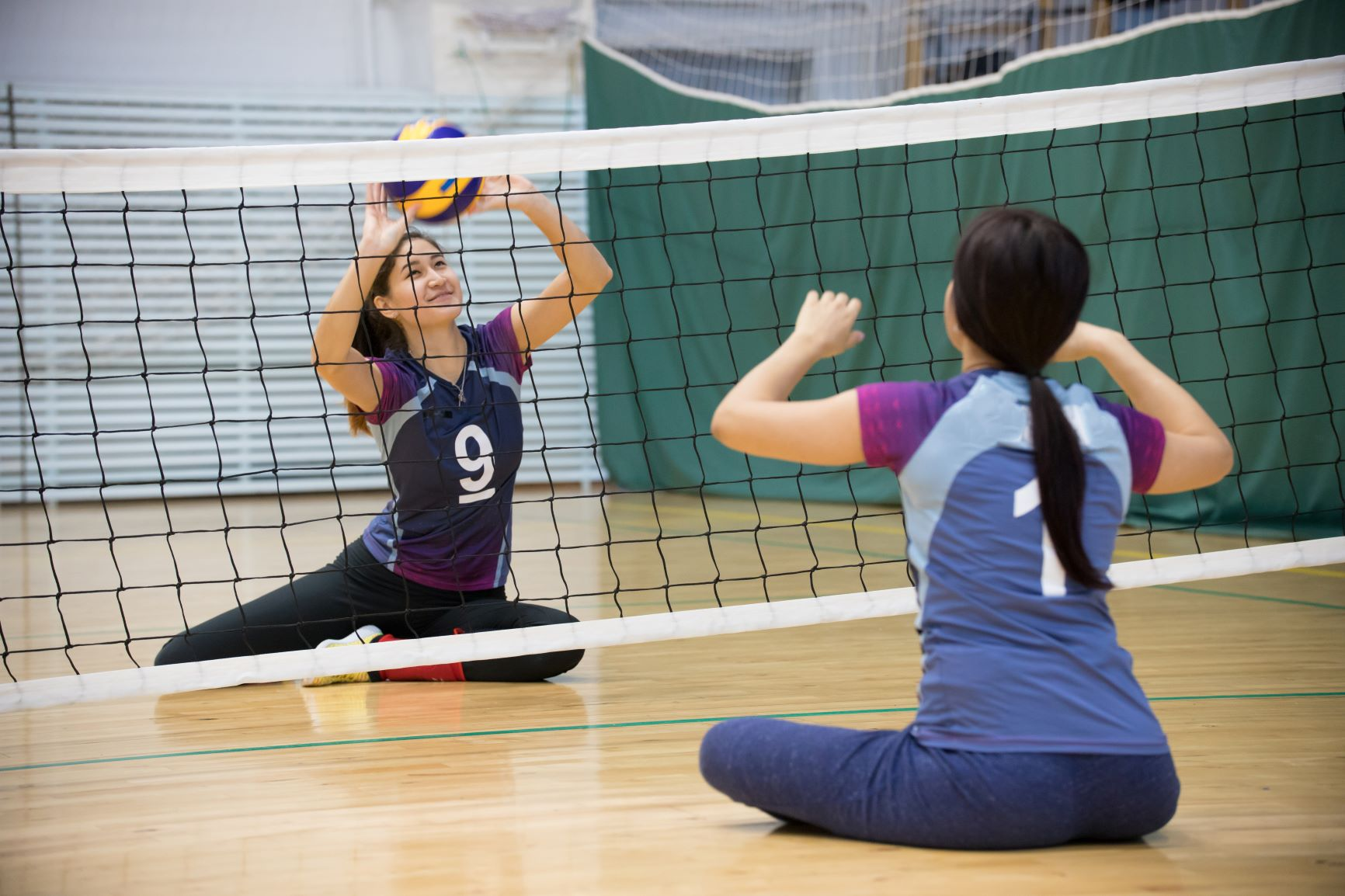 Two young women practice sitting volleyball