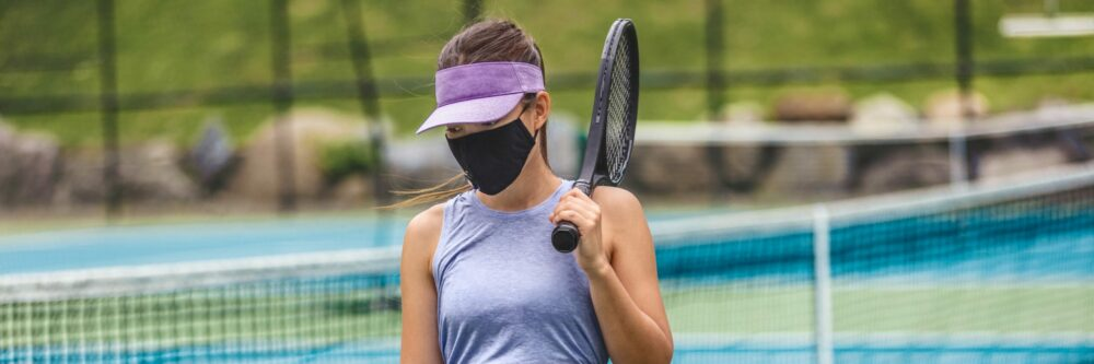 Tennis player wearing a mask.
