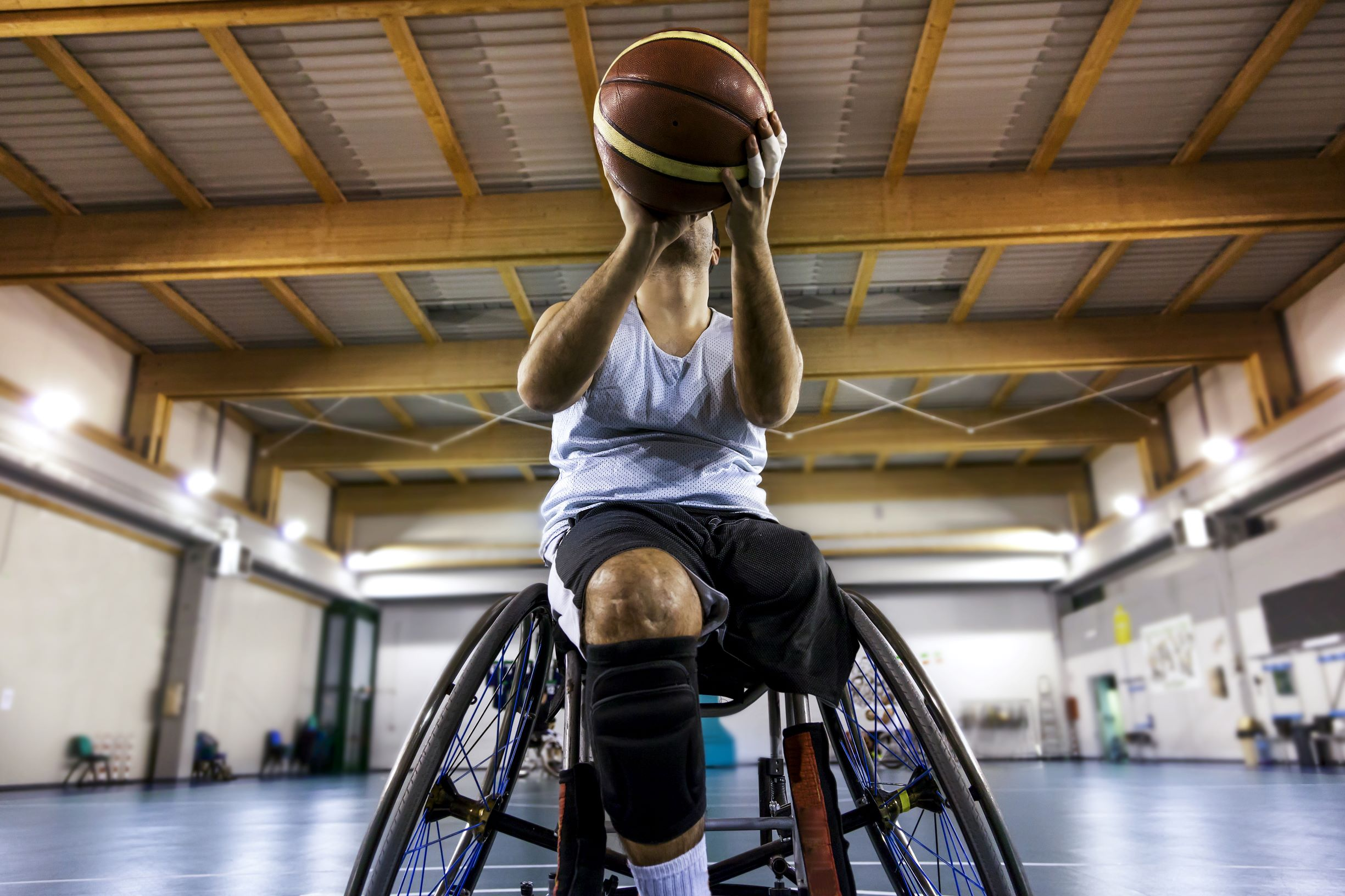 Young adult male getting ready to throw ball during wheelchair basketball game