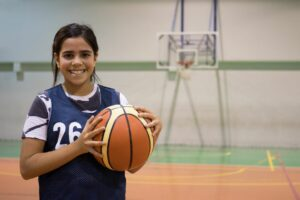 Young diverse girl holding basketball