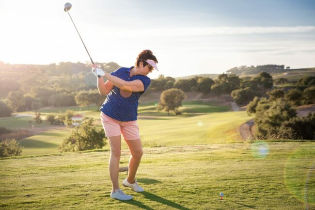 Woman golfing at sunset