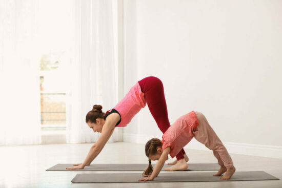 Mother practicing yoga with her daughter.