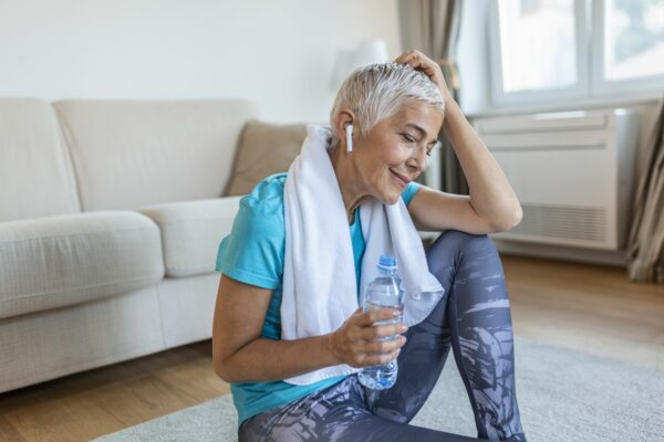 Older woman sitting, drinking water, and listening to music after working out.