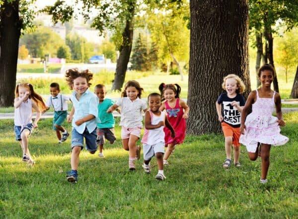 Children joyfully running through a grassy meadow.