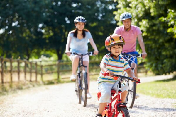 Family biking together down a gravel road during the summer.