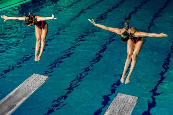 Two women synchronously jumping off diving boards.