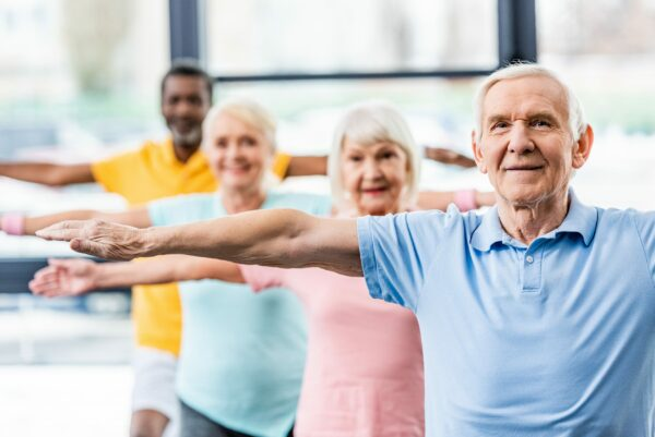 Four senior citizens stretching and taking part in an exercise class.