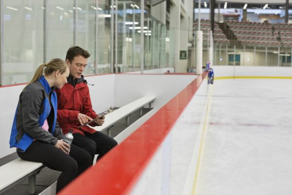 Figure skating coach on the bench showing athlete video on iPad to help improve performance.