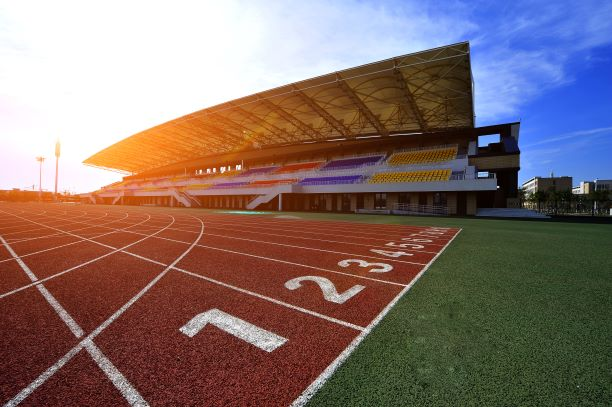 An outdoor track with colourful bleachers in the background.