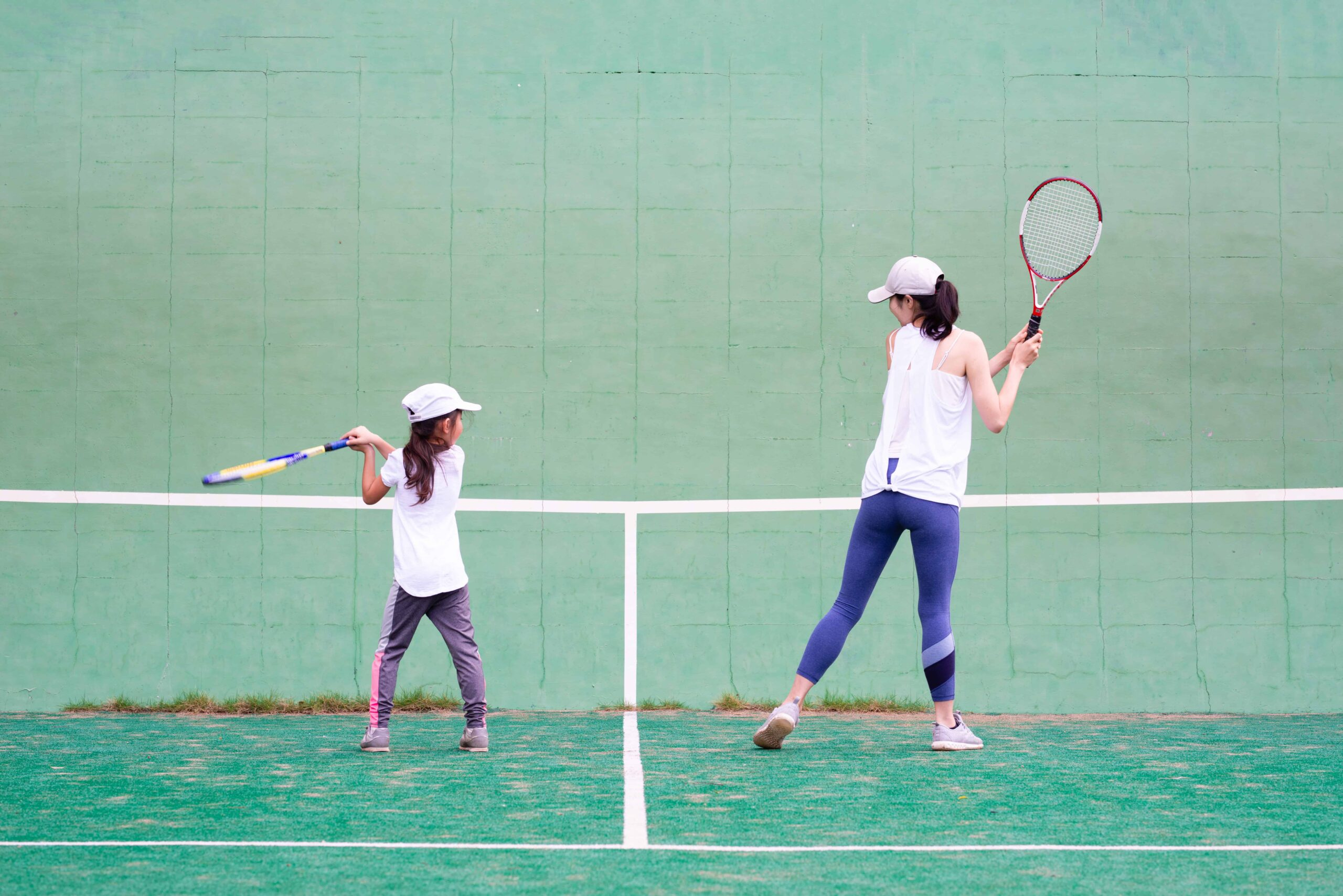 Mom and daughter practising tennis against a wall together.