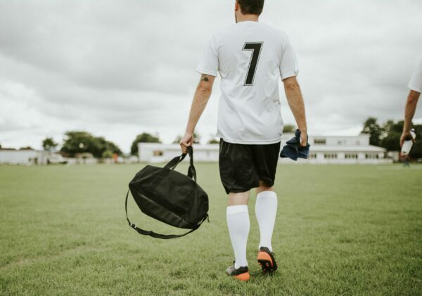 Man strolls on to a soccer pitch carrying a bag.
