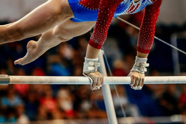 Female gymnast swinging on the high bars.