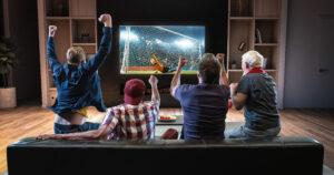 Groupe de supporters regardant un match de football sur le canapé de leur domicile. Ils célèbrent un but.