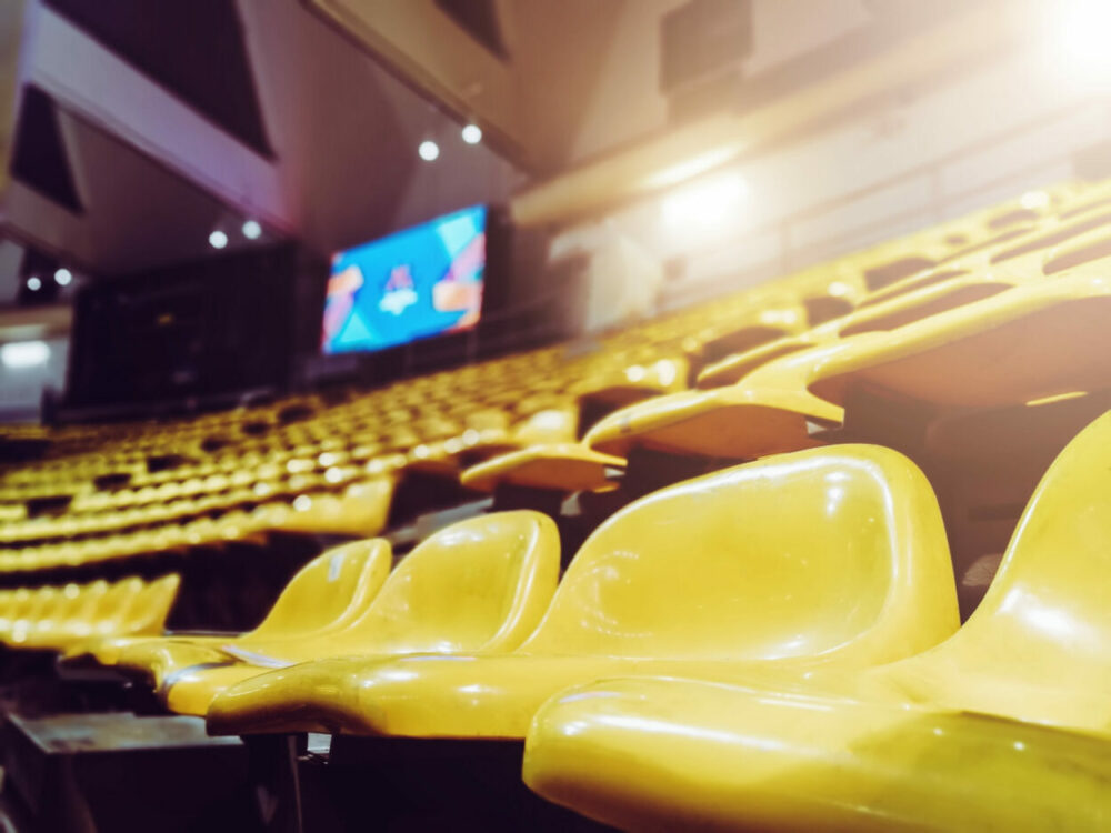 Hundreds of empty yellow seats in a stadium that has been shut off to spectators during the coronavirus pandemic.