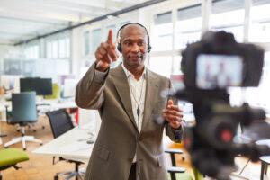 Homme portant des écouteurs parlant dans une caméra à l'intérieur d'un bureau.