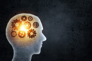 Creative silhouette image of the brain, shown with gears and lights.