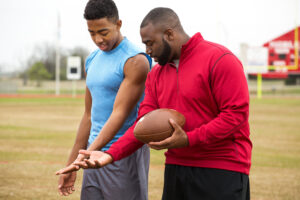 Older male athlete mentors younger male athlete in football technique