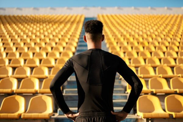 Athlete standing with his back to the camera and looking at many rows of empty seats within an empty stadium.