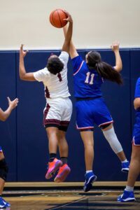 Two young female basketball athletes jump for the ball during a game.