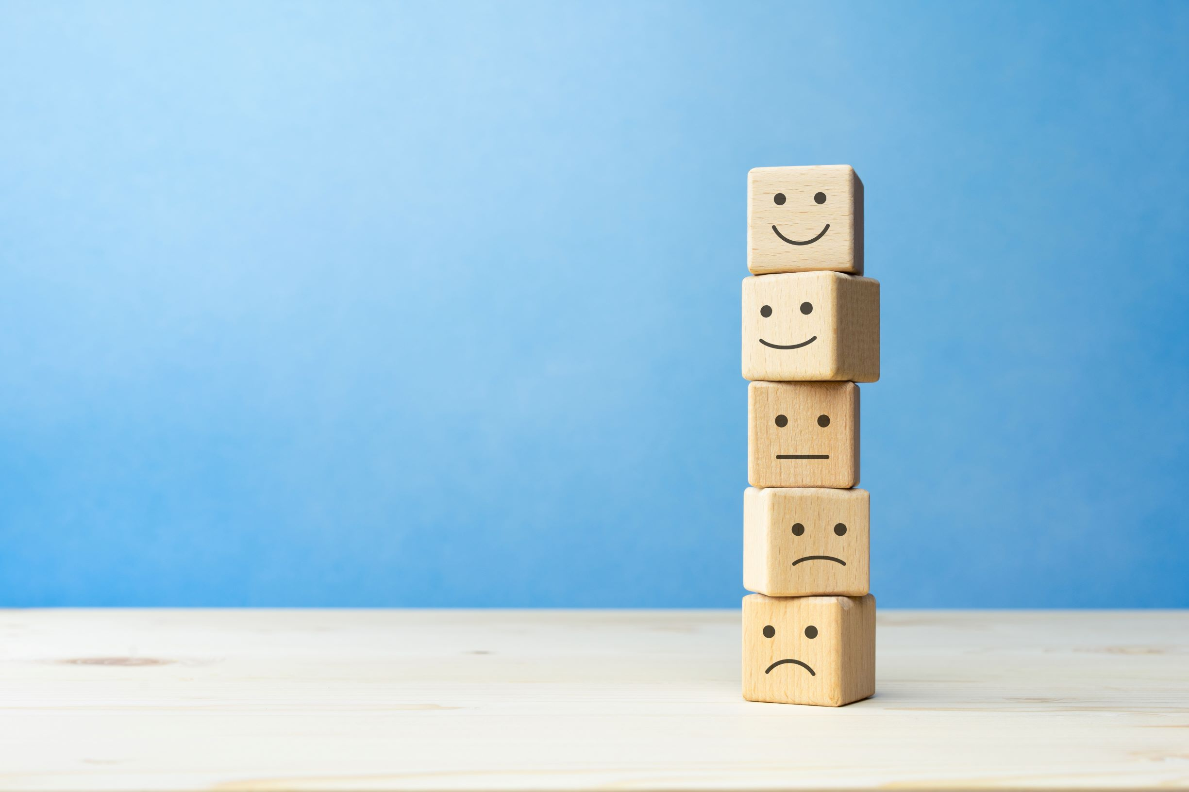 Wooden blocks stacked on a table, each has a different smiling face (happy to unhappy).