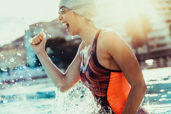 Excited female swimmer with clenched fist celebrating victory in the swimming pool.