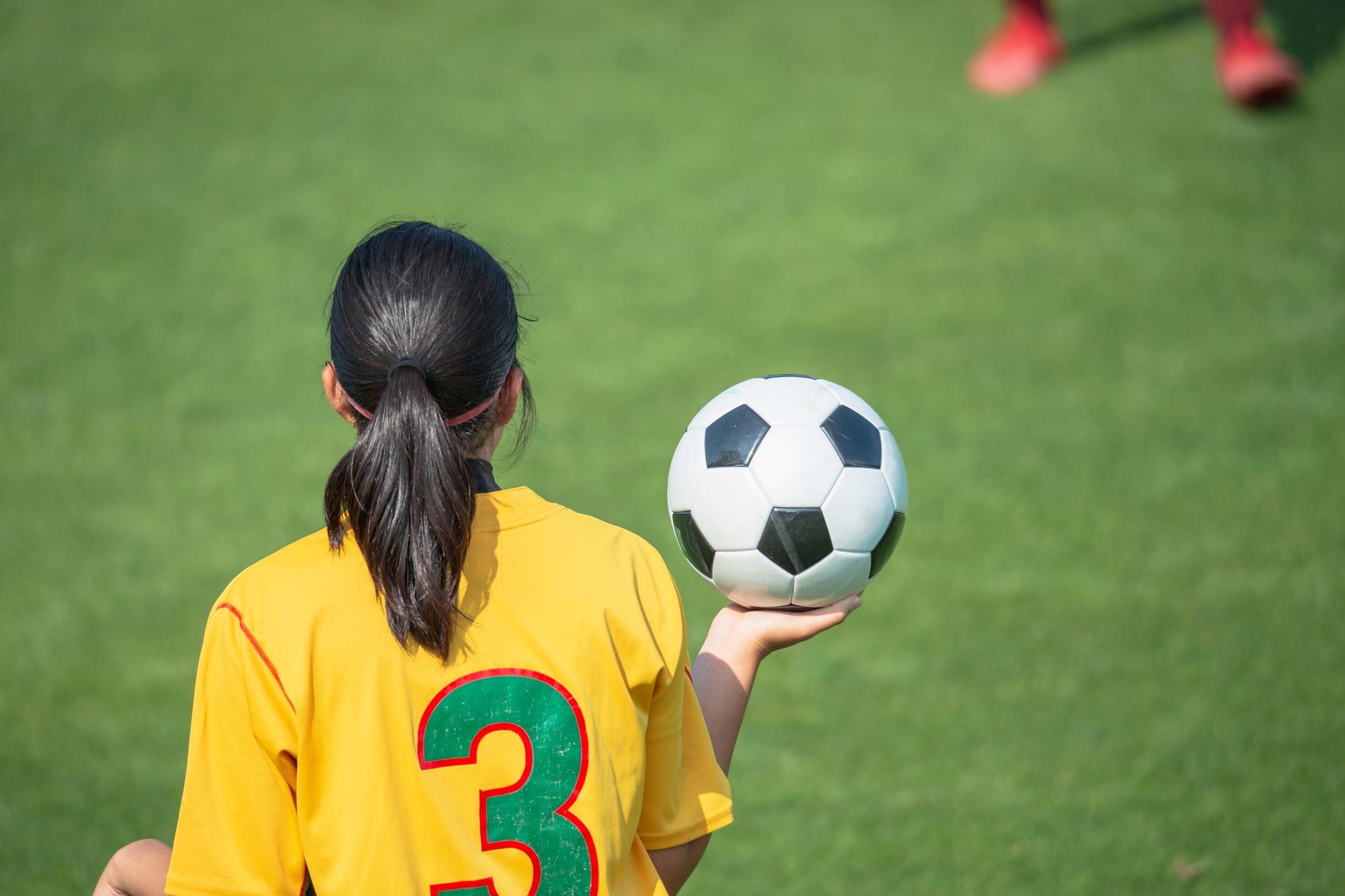 Rear view of a young girl holding a soccer ball on sidelines during a soccer match, wearing a yellow jersey.