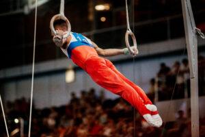 Male gymnast performing on rings.