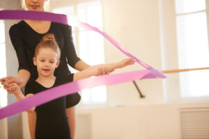 Little girl doing gymnastics moves with ribbon in studio lit by warm sunlight