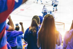 Rear view of female hockey spectators watching a hockey game in an arena.