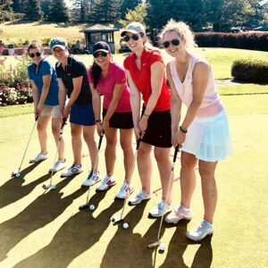 Group of women on golf course, smiling in a line. Members of Iron Lady Golf.