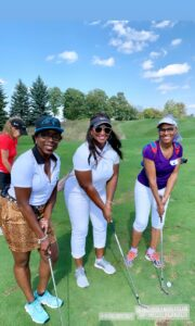 Members of Iron Lady Golf on the golf course, smiling.