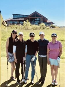 Women standing together and smiling on golf course. Members of Iron Lady Golf.