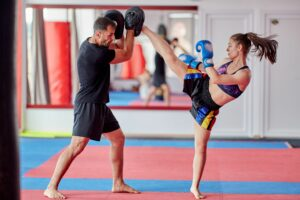 Woman training kickboxing with coach
