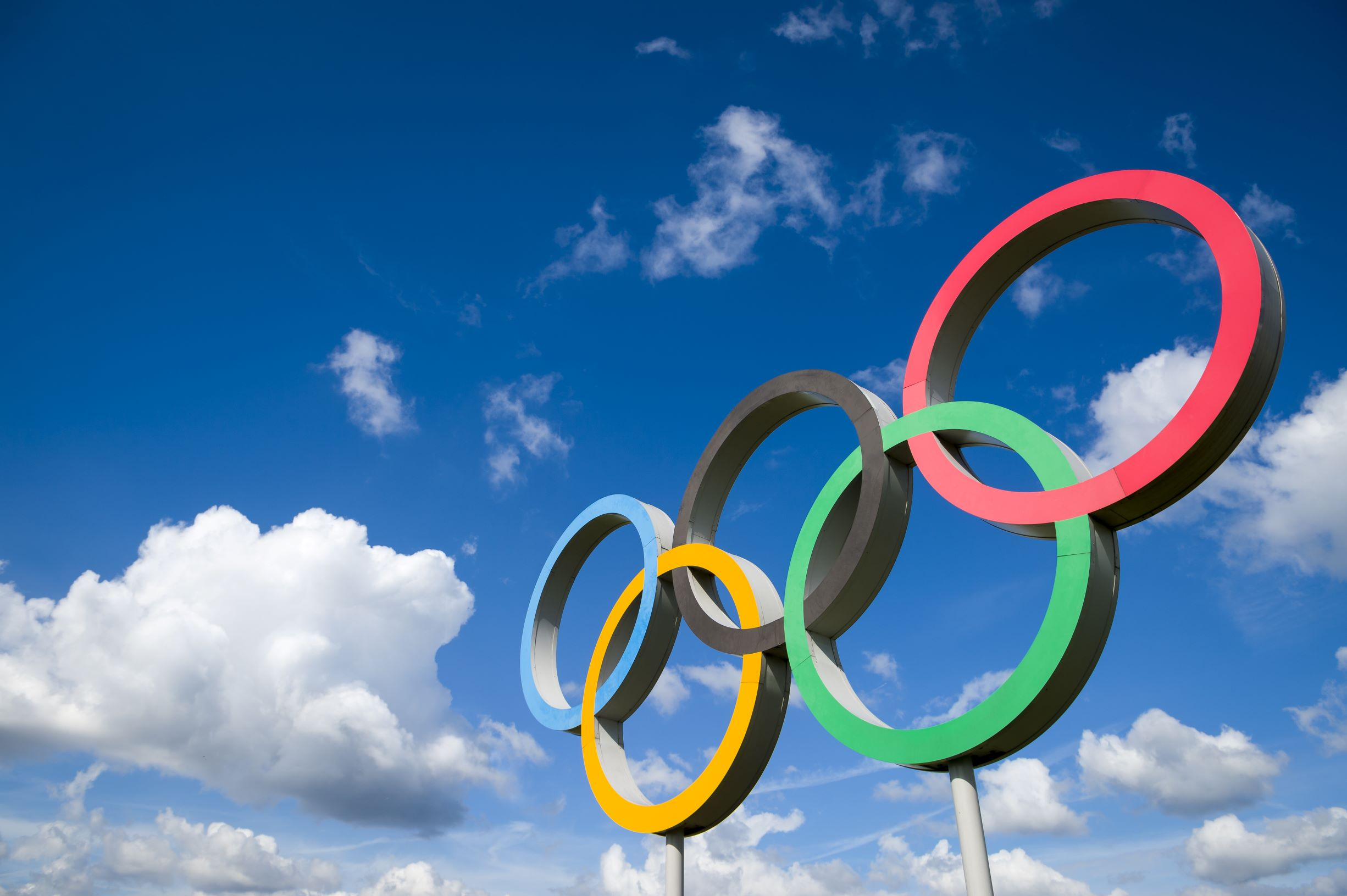 The Olympic symbol, made up of five interconnected coloured rings, under a blue sky