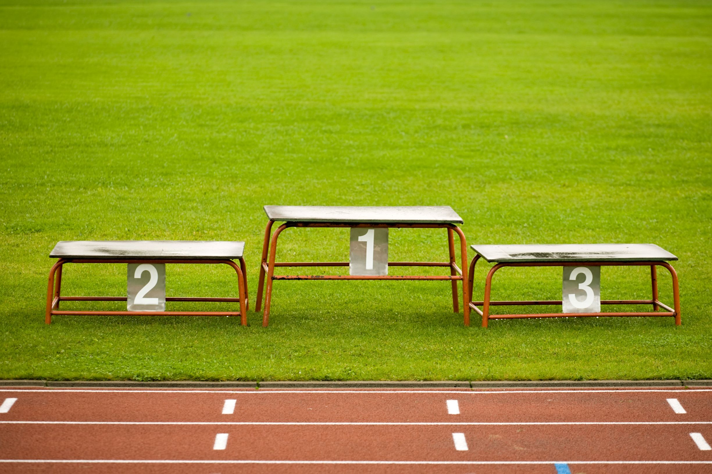 simple metal pedestal on green grass of stadium closeup