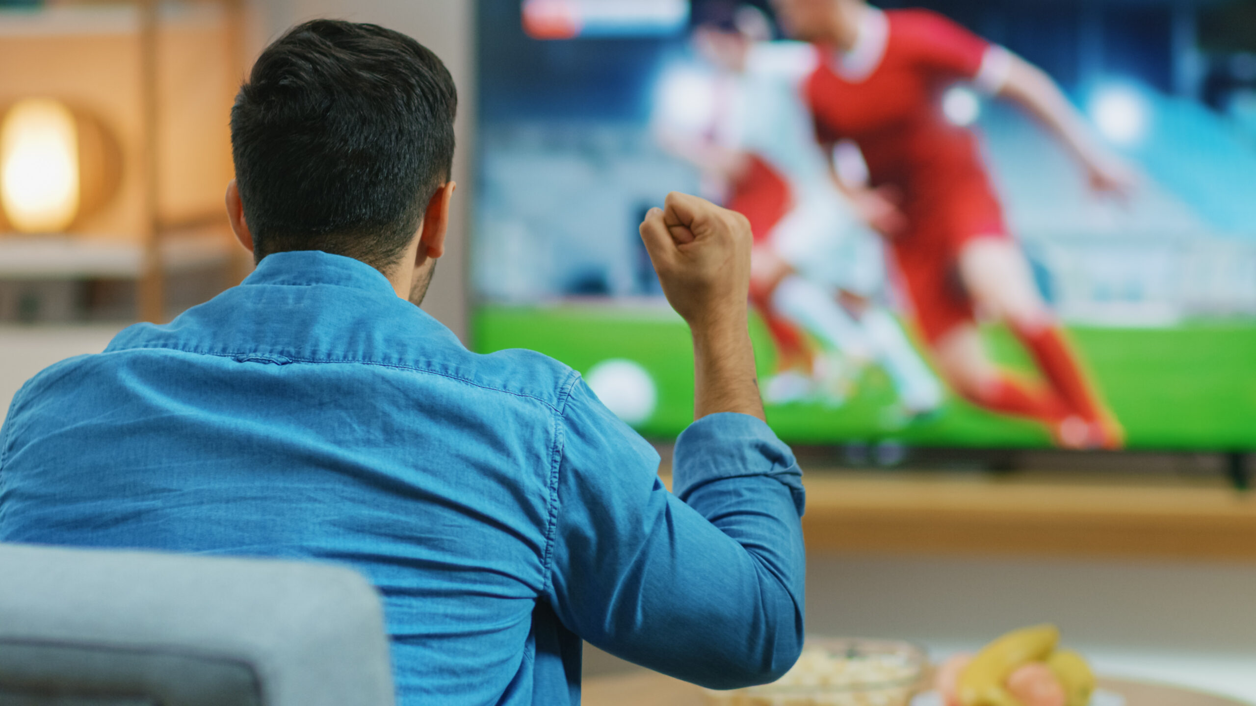 At Home Sports Fan Watches Important Soccer Match on TV, He Aggressively Clenches the Fist, Cheering for His Team.