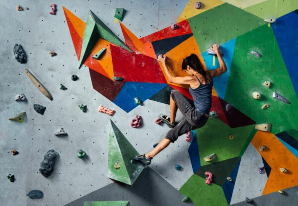 Woman rock-climbing on an artificial wall with a variety of different grips and colours.